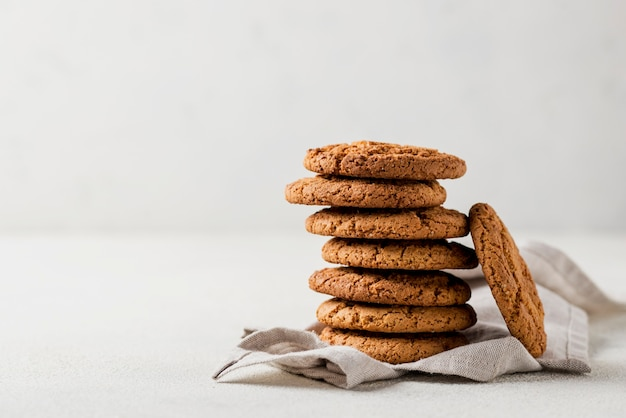 Pile of fresh baked cookies on cloth and white background