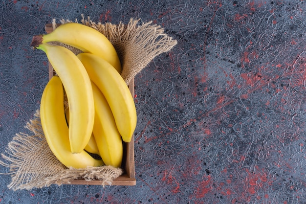 Pile of fresh banana in wooden box on colorful surface