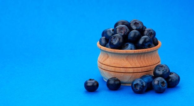 A pile of fresh blueberries in a wooden bowl
