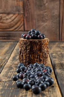 Pile of fresh blueberries in a wooden piece on wooden table