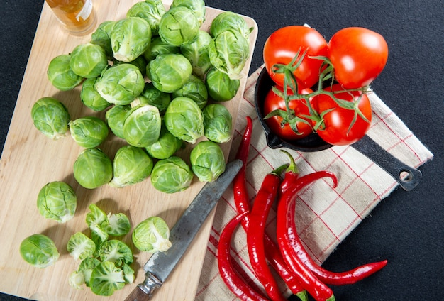 Pile of fresh brussels sprouts with tomatoes and peppers