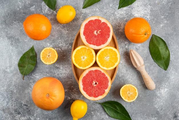 Mucchio di agrumi freschi. frutti interi o tagliati a metà su tavola di legno e superficie grigia.