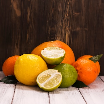 Pile of fresh citrus fruits over wooden. square image