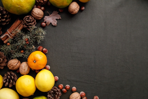 Pile of fresh fruits, cones and nuts on the dark green fabric. thanksgiving background with copyspace