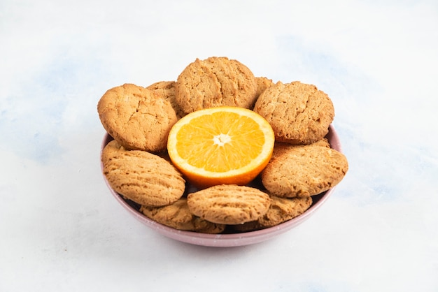 Pile of fresh homemade cookies with orange in bowl.