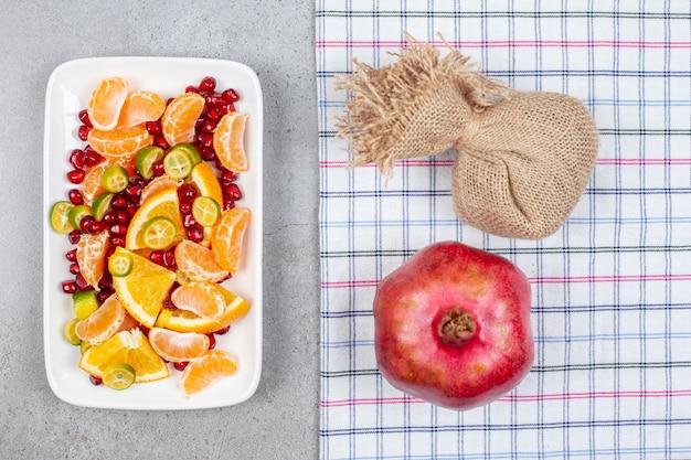 Pila di fette di frutta fresca biologica con melograno intero sul tavolo grigio. vista dall'alto .