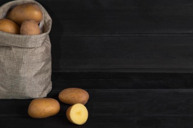 Mucchio di patate crude fresche in vecchia tela di sacco sulla superficie nera. foto di alta qualità