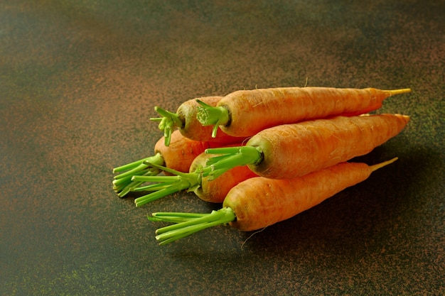 Pile of fresh ripe carrots on wooden table close-up