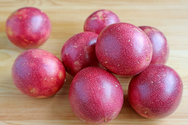 Pile of fresh ripe passion fruits on wooden background