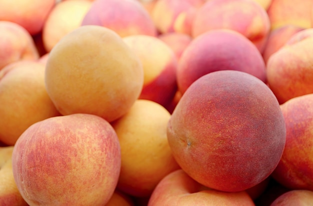 Pile of fresh ripe peaches for sale on the market