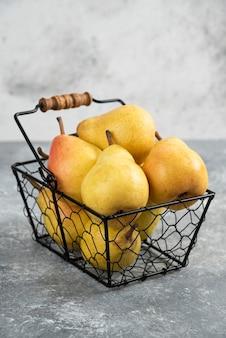 Mucchio di pere gialle fresche in secchio di metallo sulla superficie di marmo.