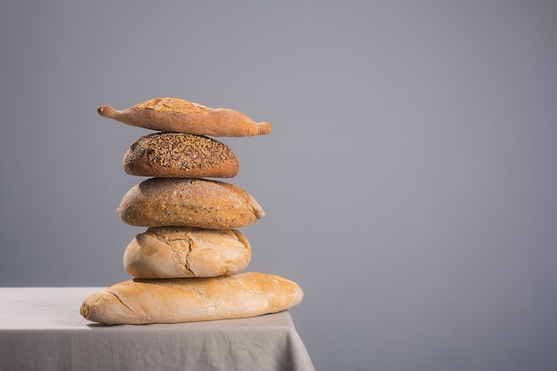 Pile of freshly baked bread on a table covered with a tablecloth with copy space