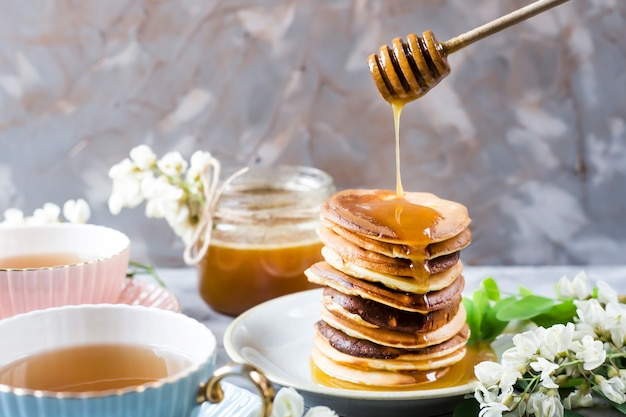 A pile of fritters next to a cup of tea and a jar of honey on a gray background