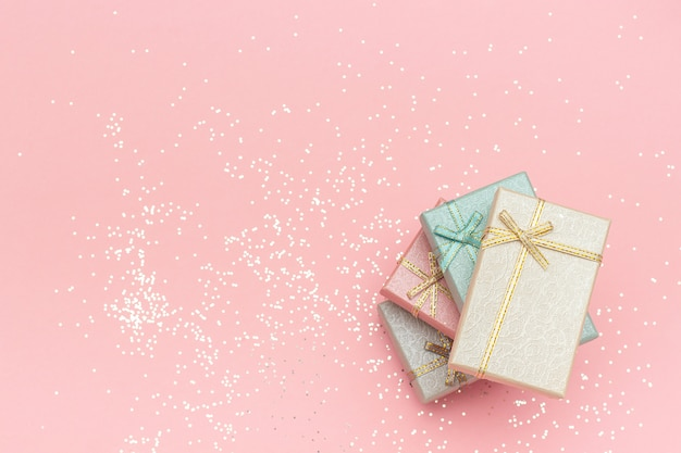 Pile gift boxes of pastel colors on pink background, top view copy space