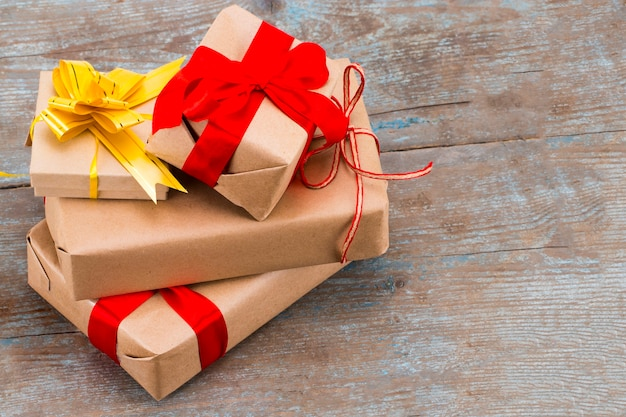 Pile gifts in kraft paper with red satin ribbon on wooden background with copy space.