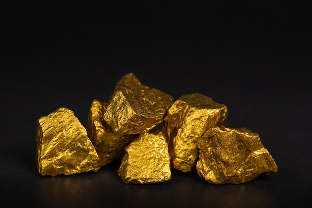 A pile of gold nuggets or gold ore on black background, precious stone or lump of golden stone, financial and business concept.