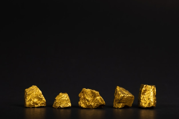 A pile of gold nuggets or gold ore on black background