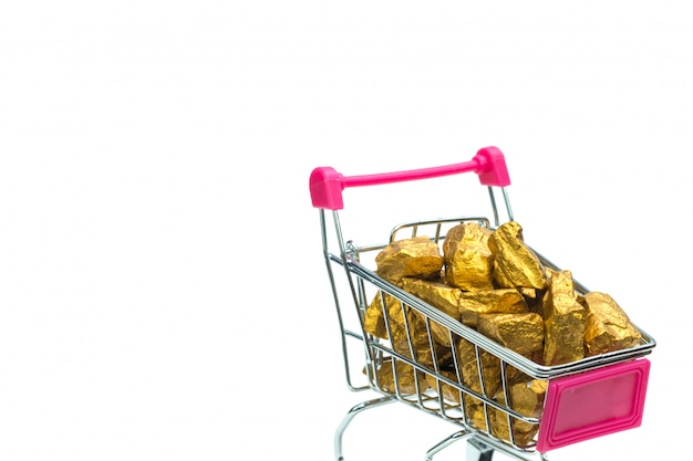 Pile of gold nuggets or gold ore in shopping cart or supermarket trolley