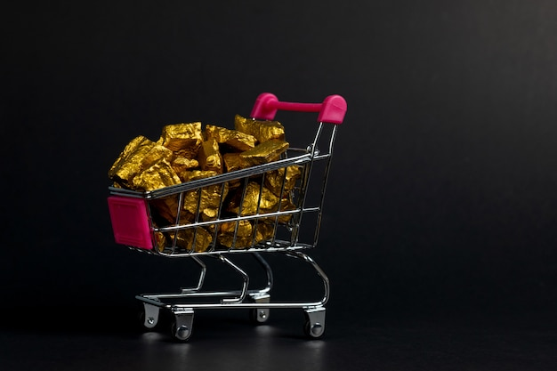 Pile of gold nuggets in shopping cart trolley