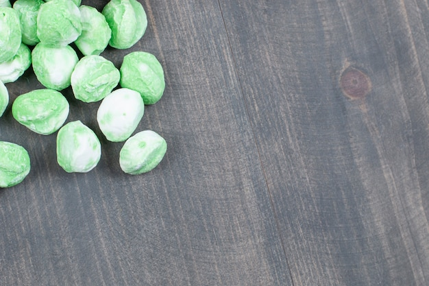 Pile of green candies on wooden surface