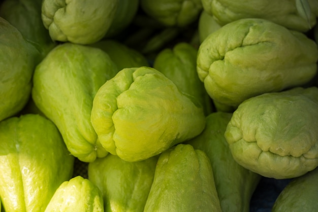 Pile of green chayote fruits.