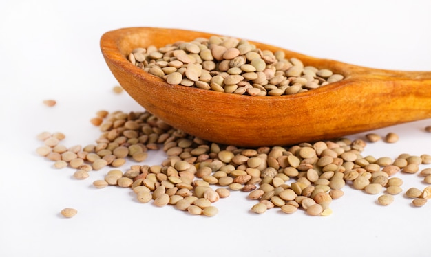 Pile of green lentils in a wooden spoon isolated on white background.