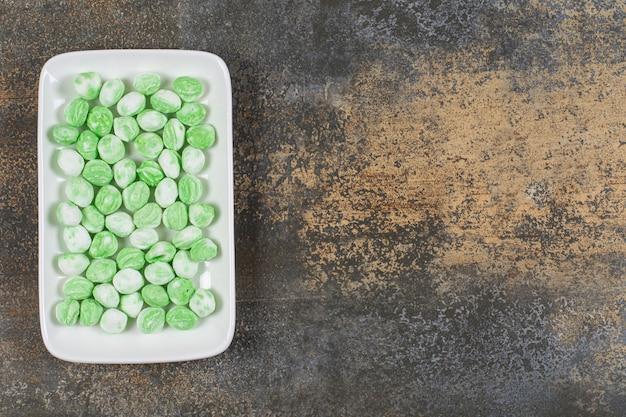 Mucchio di caramelle al mentolo verde sul piatto bianco.