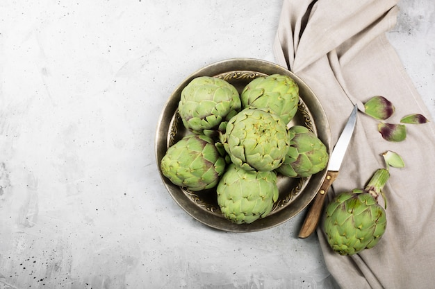 Pile of green spanish or italian artichokes on the metal rustic plate and gray table. top view with copy space