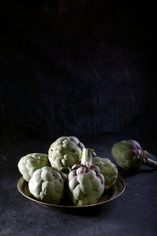 Pile of green spanish or italian artichokes on the metal rustic plate with copy space