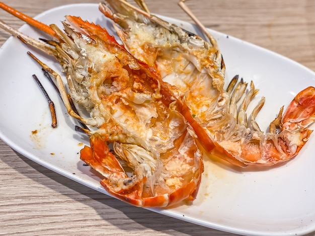 Pile of grilled giant river prawn shells on white dish on wooden table as background. popular thai food