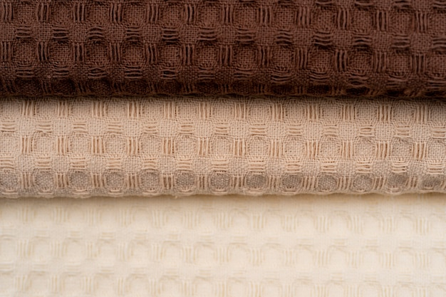 Pile of handmade dull-colored waffle linen cotton napkins towels on linen background