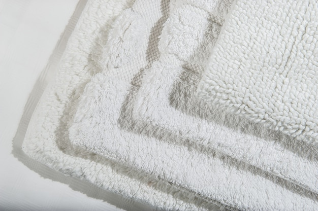 Pile of handmade waffle linen cotton napkins, towels on white linen background. different colors. food photo props. natural waffle linen cotton fabric.