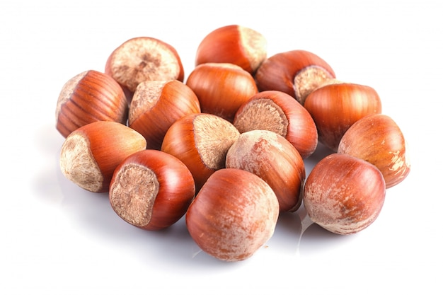Pile of hazelnuts with shell isolated on white.