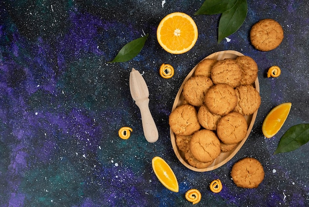 Pile of homemade fresh cookies and cookie with orange over space surface. wide angle photo.