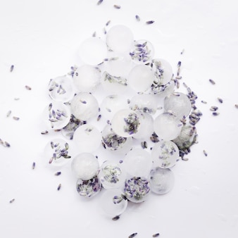 Pile of ice cubes with violet seeds
