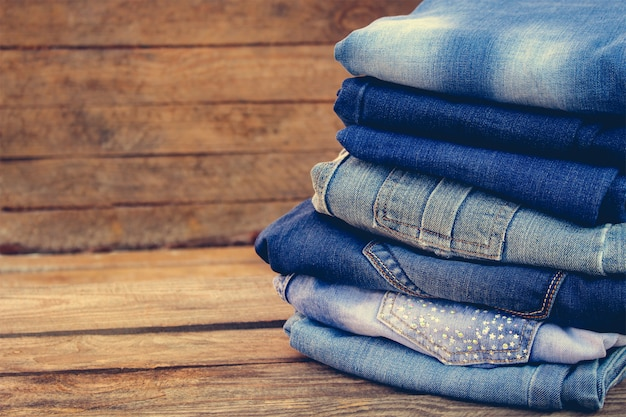 Pile of jeans clothes. toned image.