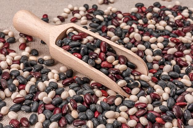 강낭콩을 흰색, 빨간색, 검은 색의 세 가지 색상으로 쌓습니다. 콩 세 가지 색상으로 나무 국자 숟가락