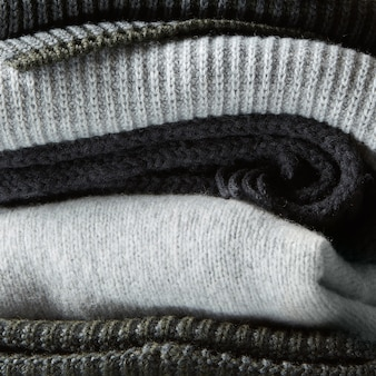 Pile of knitted winter clothes, sweaters, knitwear,