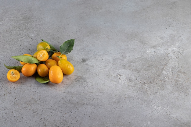A pile of kumquat fruits on the marble surface