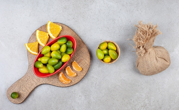 Pile of kumquats with orange and tangerine slices on wooden board .