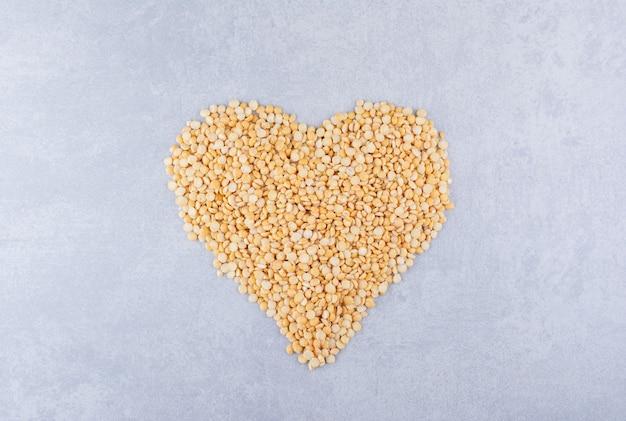 Mucchio di lenticchie disposte a forma di cuore su una superficie di marmo