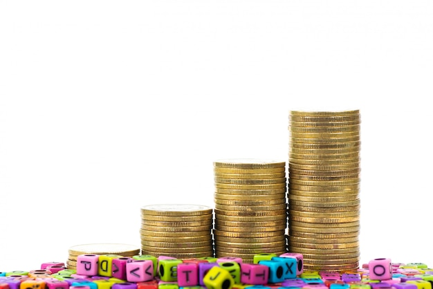 Pile of letter bead or beads with alphabet and stack of gold coin on white background.