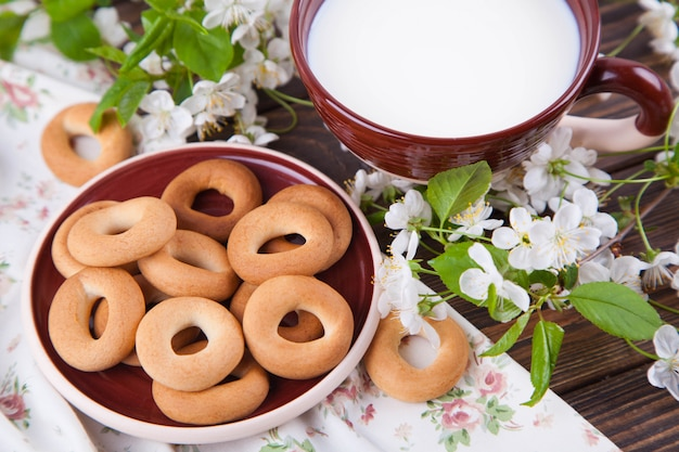 A pile of little sweet bagels on a clay plate and a cup of milk on a wooden table