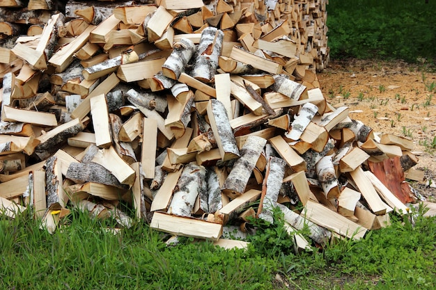 Pile of logs on the grass, chopped by an axe