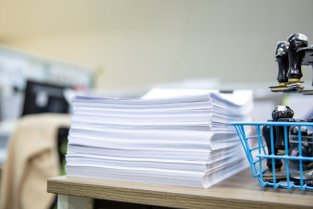 Pile of a lots paperwork  on desk office stack up