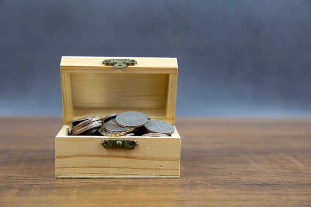 A pile of many coins in a wooden crate for money saving ideas financial planning and insurance.