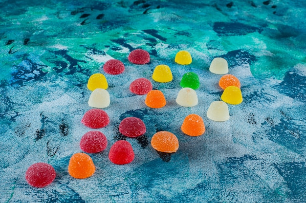 A pile of marmalade candies, on the blue background.