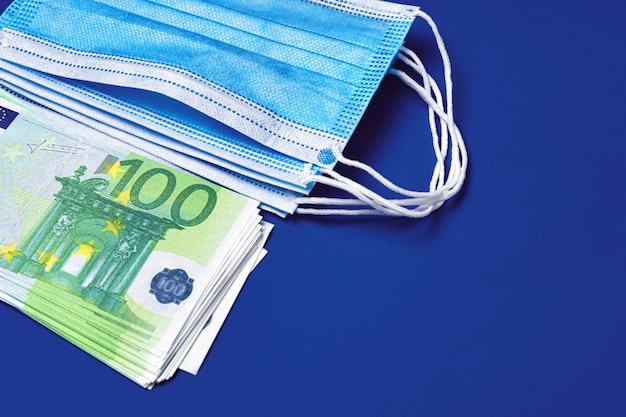 Pile of medical face masks and euro banknotes on blue background