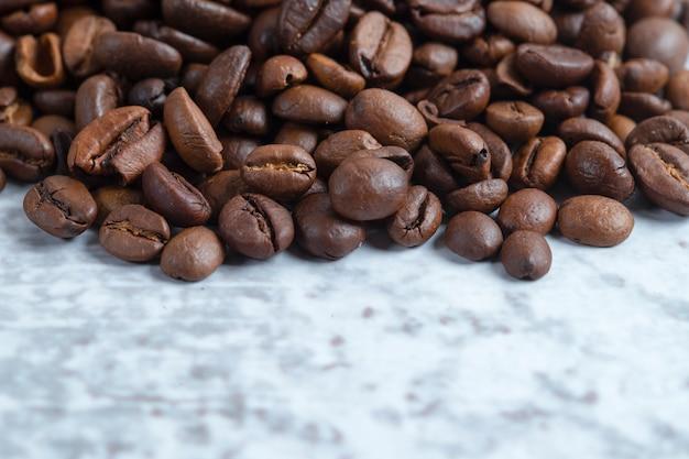 Pile of medium roasted coffee beans on stone surface.