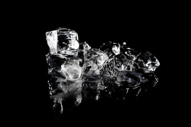 Pile of melting ice on black background